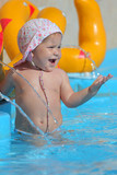 Cute toddler girl having fun in a swimming pool