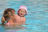 Mother with her daughter in a swimming pool