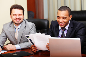 Two businesspartners joking while working in office
