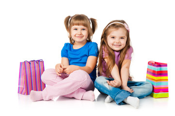 Little girls with colorful bags on white background