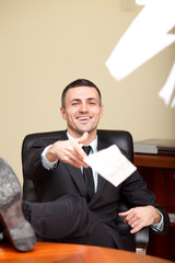 Mature relaxed handsome businessman throwing papers to camera