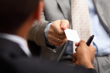 two successful business executive exchanging business card