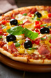 Closeup of pizza with ham, pepper and olives