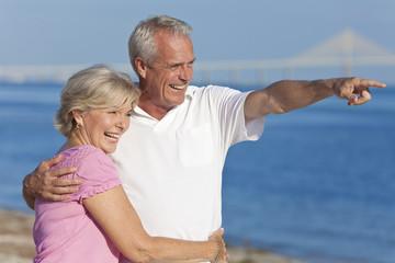 Happy Senior Couple Walking Pointing on Beach