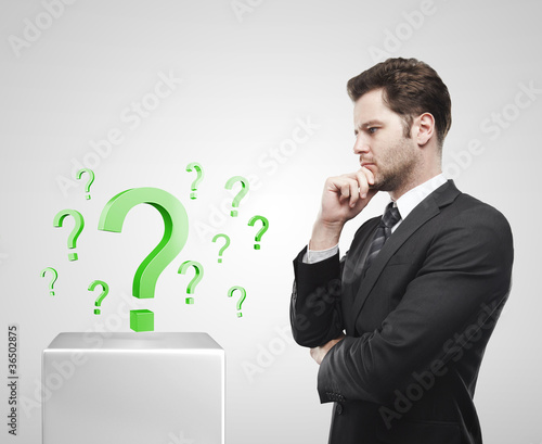 Young  businessman look at the green question marks