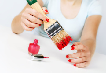 Girl paints nails with the big brush.
