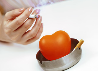 Woman's hand with a cigarette and a red heart in the ashtray.