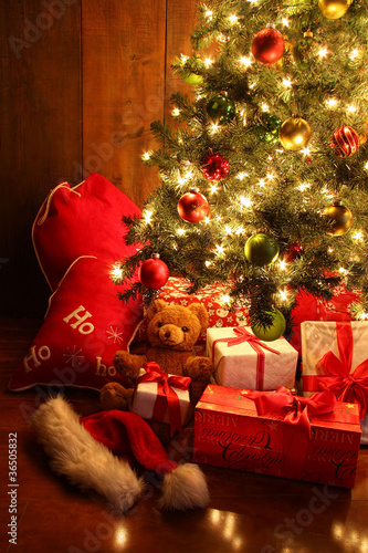 Brightly lit Christmas tree with gifts