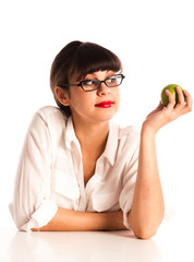 Woman at desk with green apple wearing glasses