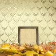 The fallen leaves on the floor and wooden picture frames