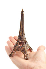 Hand holding small Eiffel Tower statuette