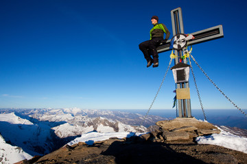 Young man sitting on a summit cross in the Alps