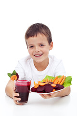 Healthy child with fresh beetroot juice and vegetable slices