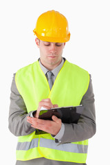 Portrait of a young builder taking notes