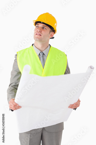 Portrait of a builder looking around while holding a plan