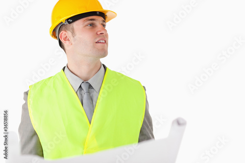 Builder holding a plan while looking around
