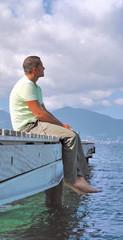 Homme de 40 ans assis face à la mer