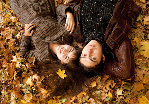 Couple lying in the park in fall