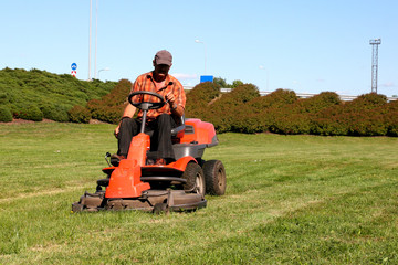 Mature man driving grass cutter