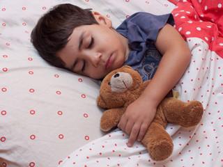 bambino che dorme nel letto con orsetto