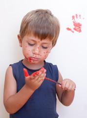 bambino che pittura di rosso le mani