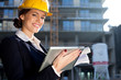 Attractive happy female construction engineer/architect with a t
