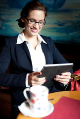 Young businesswoman using her tablet computer on a coffee break.