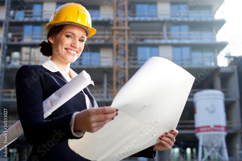 Young female architect/construction engineer at a construction s
