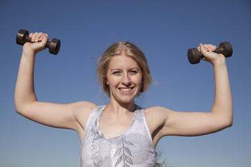 woman weights up blue sky