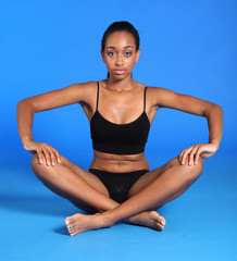 Athletic african fitness woman sits cross legged