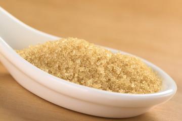 Brown granulated cane sugar on ceramic spoon