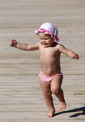 Cute toddler girl running on wooden floor
