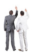 Back view of two businessman pointing at wall. rear view. Isolat