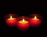 Votive candles in red holders over black