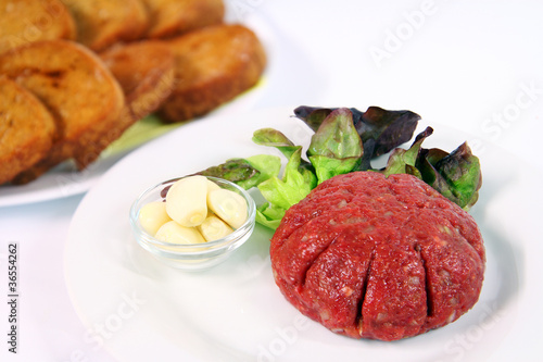 Steak tartare with garlic on white plate with onions and toast