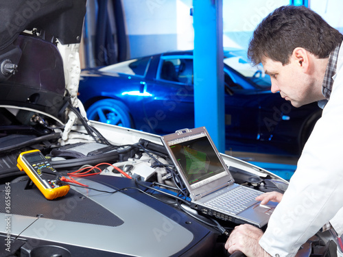 Motor mechanic is tuning and checking the engine of a car - 36554854