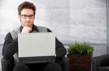 Young man browsing internet on laptop