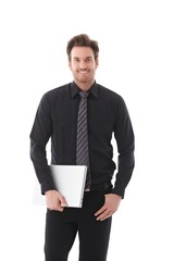 Young businessman holding laptop smiling