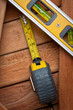 Spirit level and measuring tape over wooden boards