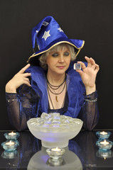 Witch in blue hat with magic cristalls and candles