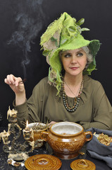 Magic woman in green hat with smoking twigs