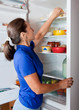 woman taking something of the fridge