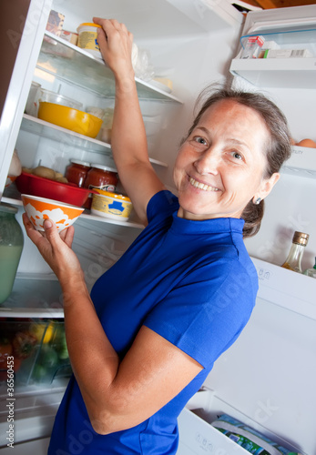 Ordinary woman taking something of the fridge