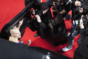 Celebrity emerging from car towards paparazzi