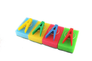 Color sponges and clothes-pegs over white