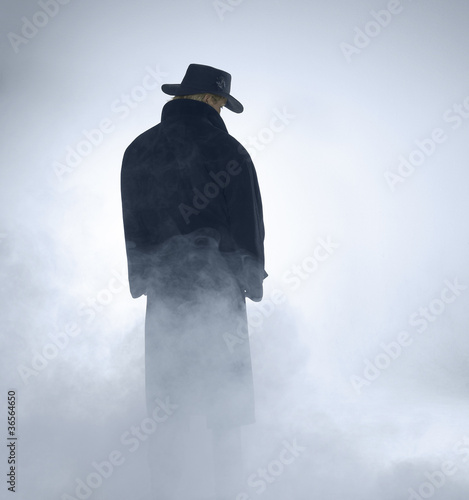 Woman wearing trench coat and standing in fog