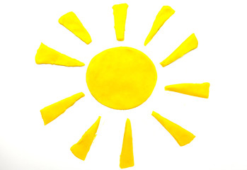 Painted yellow sun of plasticine on background
