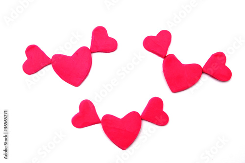 Painted pink hearts of plasticine on background