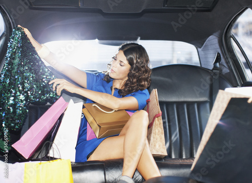 Woman with shopping bags in backseat of limo