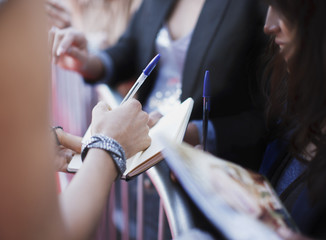 Celebrity signing autographs for fan